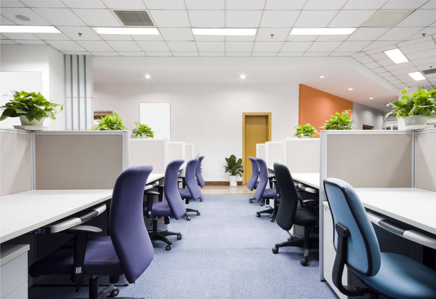 an interior view of a modern office space with desks and chairs