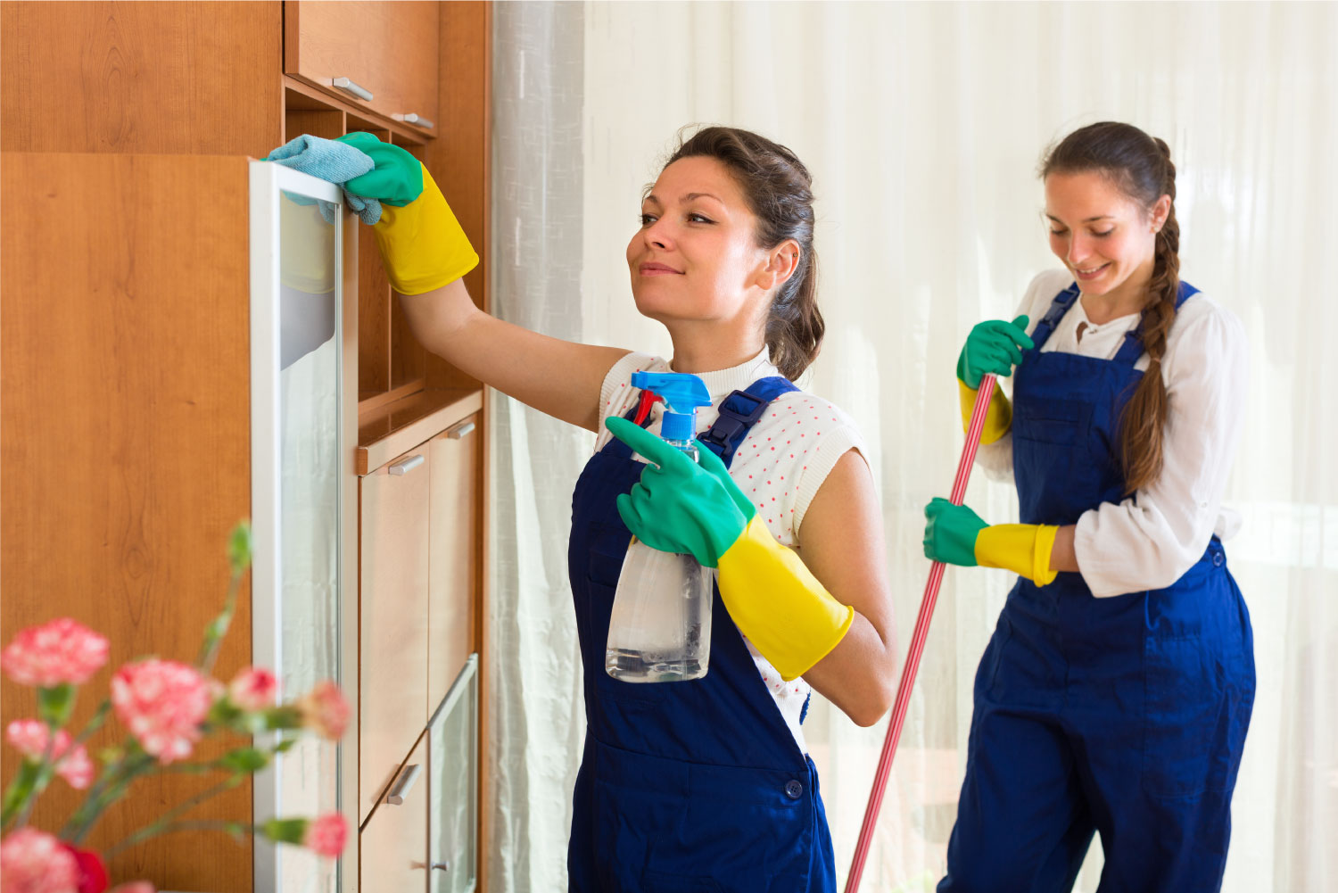 two female cleaners cleaning a kitchen