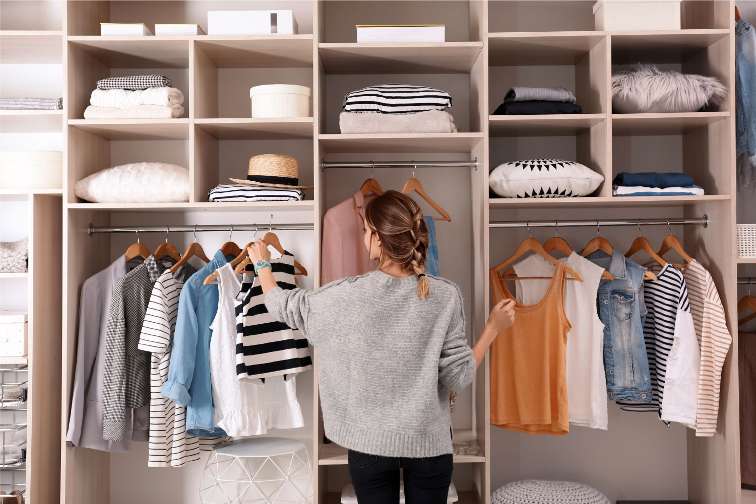 a woman selecting clothes from a neatly organised wardrobe